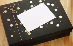 Όμορφο κιβώτιο δώρων με τη χρυσά κορδέλλα και το τόξο και κενή κάρτα για το κείμενο στοκ φωτογραφία
