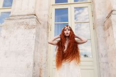 Όμορφο κοκκινομάλλες κορίτσι με τη μακριά σγουρή τρίχα στη νύφη, σε ένα μακρύ φόρεμα δαντελλών Μια φυσική ομορφιά Στοκ φωτογραφία με δικαίωμα ελεύθερης χρήσης