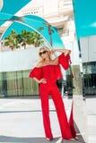 Όμορφο κομψό θηλυκό πρότυπο μόδας στο κόκκινο φόρεμα που στέκεται μπροστά από τα ξενοδοχεία πολυτελείας και τις μπουτίκ Στοκ φωτογραφία με δικαίωμα ελεύθερης χρήσης