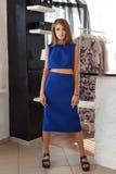 Όμορφο κομψό καθιερώνον τη μόδα μοντέρνο νέο κορίτσι με το μακρυμάλλες και φωτεινό makeup στην μπλε τοποθέτηση φορεμάτων για τη κ Στοκ Εικόνα