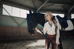 Όμορφο κομψό νέο ξανθό κορίτσι που στέκεται κοντά στο άλογό της που ντύνει τον ομοιόμορφο ανταγωνισμό στοκ φωτογραφία