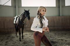 Όμορφο κομψό νέο ξανθό κορίτσι που στέκεται κοντά στο άλογό της που ντύνει τον ομοιόμορφο ανταγωνισμό στοκ εικόνες