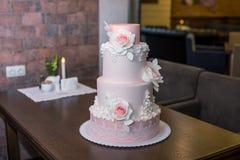 Όμορφο κομψό τοποθετημένο στη σειρά ρόδινο γαμήλιο τέσσερα κέικ που διακοσμείται με τα λουλούδια τριαντάφυλλων Έννοια floral από  Στοκ Εικόνες