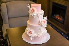 Όμορφο κομψό τοποθετημένο στη σειρά ρόδινο γαμήλιο τέσσερα κέικ που διακοσμείται με τα λουλούδια τριαντάφυλλων Έννοια floral από  Στοκ εικόνες με δικαίωμα ελεύθερης χρήσης