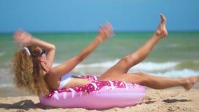 Όμορφο κορίτσι διογκώσιμο doughnut που χορεύει ενάντια στη θάλασσα φιλμ μικρού μήκους