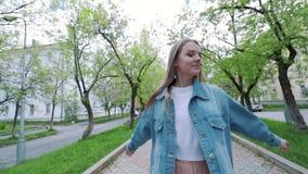 Όμορφο κορίτσι εφήβων που ακούει τη μουσική που περπατά κατά μήκος των ηλικιωμένων οδών πόλεων και της χορεύοντας ευτυχούς γυναίκ φιλμ μικρού μήκους