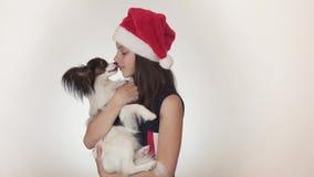 Όμορφο κορίτσι εφήβων σε έναν Άγιο Βασίλη ΚΑΠ και το ηπειρωτικό σπανιέλ Papillon παιχνιδιών σκυλιών χαρωπά που φιλά και που γύρω  φιλμ μικρού μήκους
