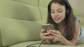 Όμορφο κορίτσι εφήβων στα ακουστικά που τραγουδούν τα τραγούδια καραόκε στο βίντεο μήκους σε πόδηα αποθεμάτων smartphone απόθεμα βίντεο