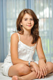 Όμορφο κορίτσι εφήβων στο σπίτι στο άσπρο φόρεμα Στοκ Εικόνες