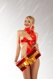 Όμορφο κορίτσι διασκέδασης με το μεγάλο δώρο και κόκκινες κορδέλλες στο λεπτό σώμα Στοκ Εικόνα