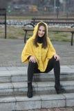 Όμορφο κορίτσι κίτρινο χειροποίητο πλεκτό poncho Στοκ Εικόνες