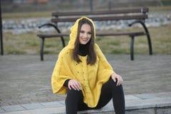 Όμορφο κορίτσι κίτρινο χειροποίητο πλεκτό poncho Στοκ Φωτογραφία