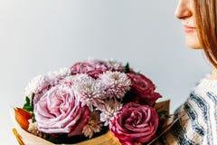 Όμορφο κορίτσι και πορφυρή ανθοδέσμη λουλουδιών τριαντάφυλλων Στοκ Εικόνες