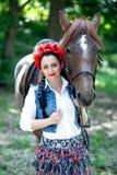 Όμορφο κορίτσι κοντά στο καφετί άλογο Στοκ Εικόνα