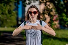 Όμορφο κορίτσι μαθητριών Θερινή φύση μετά από το σχολείο Τα γυαλιά, καρδιά διαμορφώνονται Χαμογελά ευτυχώς Οι χειρονομίες των χερ Στοκ φωτογραφίες με δικαίωμα ελεύθερης χρήσης