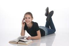 Όμορφο κορίτσι με ένα βιβλίο και ένα τηλέφωνο σε ένα άσπρο υπόβαθρο Στοκ Φωτογραφίες