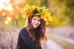 Όμορφο κορίτσι με ένα στεφάνι των κίτρινων φύλλων στο κεφάλι Στοκ Φωτογραφίες