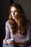 Όμορφο κορίτσι με ένα φλυτζάνι στα χέρια της που φαίνονται παράθυρο Στοκ Φωτογραφίες