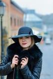 Όμορφο κορίτσι με ένα χαμόγελο στους περιπάτους καπέλων γύρω από την πόλη Στοκ Φωτογραφία