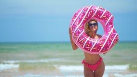 Όμορφο κορίτσι με διογκώσιμο doughnut που χορεύει ενάντια στη θάλασσα απόθεμα βίντεο