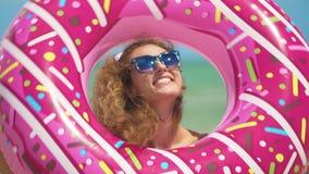 Όμορφο κορίτσι με διογκώσιμο doughnut που χορεύει ενάντια στη θάλασσα E απόθεμα βίντεο