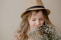 Όμορφο κορίτσι με μακρυμάλλη σε ένα καπέλο με τα λουλούδια στοκ εικόνα