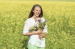 Όμορφο κορίτσι με μια ανθοδέσμη στον τομέα στοκ φωτογραφία