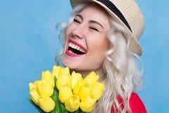 Όμορφο κορίτσι με μια ανθοδέσμη των γέλιων Στοκ Εικόνες