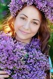 Όμορφο κορίτσι με μια ανθοδέσμη των πασχαλιών και ένα στεφάνι της πασχαλιάς Στοκ Εικόνες