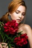 Όμορφο κορίτσι με μια ανθοδέσμη των peonies Πρότυπο με μια ευγενή σύνθεση Πρόσωπο ομορφιάς στοκ φωτογραφίες