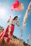 Όμορφο κορίτσι με πολλά χρωματισμένα μπαλόνια υπό εξέταση στοκ εικόνες