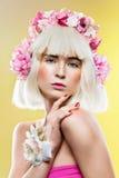 Όμορφο κορίτσι με τα ακουστικά λουλουδιών στοκ εικόνα