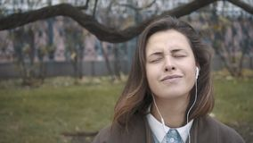 Όμορφο κορίτσι με τα ακουστικά που ακούει τη μουσική φιλμ μικρού μήκους