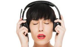 Όμορφο κορίτσι με τα ακουστικά που απομονώνεται στο λευκό Στοκ Φωτογραφίες