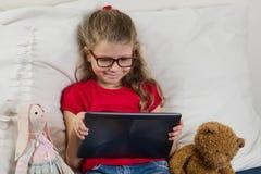 Όμορφο κορίτσι με τα γυαλιά που προσέχει τα κινούμενα σχέδια, βίντεο σε την ταμπλέτα α Στοκ Φωτογραφία