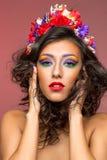 Όμορφο κορίτσι με τα εξαρτήματα λουλουδιών Στοκ Φωτογραφία
