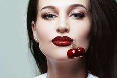 Όμορφο κορίτσι με τα κεράσια στο στόμα της Στοκ Εικόνες