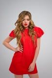 Όμορφο κορίτσι με τα κυματιστά ξανθά μαλλιά στην κόκκινη τοποθέτηση φορεμάτων Στοκ Φωτογραφία