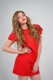 Όμορφο κορίτσι με τα κυματιστά ξανθά μαλλιά στην κόκκινη τοποθέτηση φορεμάτων Στοκ Φωτογραφίες
