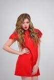 Όμορφο κορίτσι με τα κυματιστά ξανθά μαλλιά στην κόκκινη τοποθέτηση φορεμάτων Στοκ Εικόνα