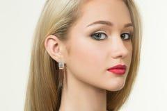 Όμορφο κορίτσι με τα κόκκινα χείλια και τα σκουλαρίκια Μόδα στοκ εικόνες