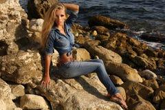 Όμορφο κορίτσι με τα μακριά ξανθά μαλλιά στα ενδύματα τζιν που θέτουν στη θερινή παραλία Στοκ Εικόνες