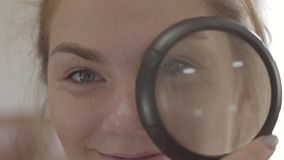Όμορφο κορίτσι με τα μπλε μάτια που κοιτάζει στη κάμερα μέσω της κινηματογράφησης σε πρώτο πλάνο loupe Θετικός τρόπος ζωής Πρόσωπ απόθεμα βίντεο