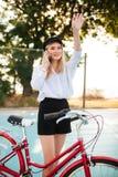 Όμορφο κορίτσι με τα ξανθά μαλλιά στο πουκάμισο και σορτς που στέκονται με το κόκκινο ποδήλατο στο γήπεδο μπάσκετ στο πάρκο και χ Στοκ εικόνες με δικαίωμα ελεύθερης χρήσης