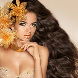 Όμορφο κορίτσι με τα χρυσά λουλούδια Πρότυπο πρόσωπο γυναικών ομορφιάς ανά Στοκ Φωτογραφία