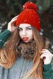 Όμορφο κορίτσι με τα όμορφα μπλε μάτια σε μια κόκκινη στάση καπέλων και παλτών Στοκ Εικόνες