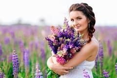 Όμορφο κορίτσι με την ανθοδέσμη των λουλουδιών lupine στα χέρια στοκ εικόνες