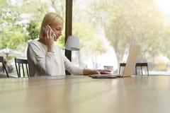 Όμορφο κορίτσι με την κοντή τρίχα που μιλά σε ένα τηλέφωνο κυττάρων καθμένος σε έναν καφέ Στοκ Φωτογραφίες