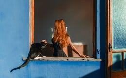 Όμορφο κορίτσι με την κόκκινη τρίχα και γάτα στο παράθυρο Στοκ Εικόνα