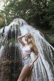 Όμορφο κορίτσι με την ξανθή σγουρή τοποθέτηση τρίχας κοντά στον καταρράκτη Στοκ φωτογραφίες με δικαίωμα ελεύθερης χρήσης